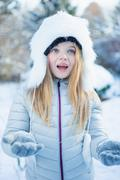 Cute girl throwing snowflake on a beautiful snowy day Stock Photos