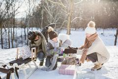 Happy family holding presents on a beautiful snowy day Stock Photos