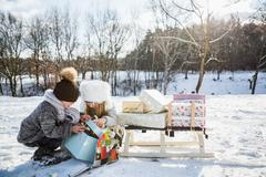 Brother and sister opening present on a beautiful snowy day Stock Photos