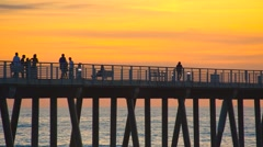 Woman running down boardwalk during sunset - stock footage