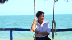 Senior Asian woman relax on the swing at the beach with blue sea background Stock Footage