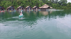Ban Wang Khon, Surat Thani, Canoeing Woman with Huts In Background Stock Footage
