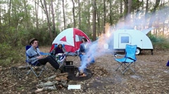 Family camping with campfire, tent, and teardrop trailer in the forest Stock Footage
