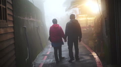 Asian senior couple walking and holding hands together in the mist Stock Footage
