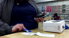 People using credit card to return wireless game controller inside Apple store - stock footage