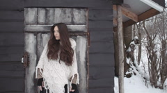 Young brunette woman wearing knitted sweater standing by the wooden house. Stock Footage