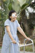 Elderly use eye shield covering after cataract surgery in backyard. Kuvituskuvat
