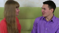 Beautiful young man with woman sitting on couch. Guy gives the girl a gift - stock footage