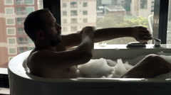 Young man washing his arms lying inin bathtub with city view Stock Footage