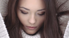 Beautiful natural face of young brunette woman in woollen hood. - stock footage