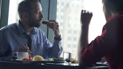 Young couple eating breakfast by table close to the window with city view - stock footage