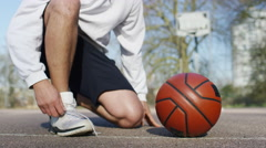 4K Shoelace being tied up next to a basketball as unseen man does sprint drills Stock Footage
