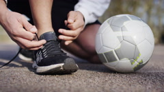 4K Shoelace being tied up next to a soccer ball as unseen man does sprint drills Stock Footage