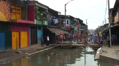 Colorful houses by the river in Belen in Iquitos bustling with people - stock footage
