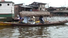 Floating market in the floating village in the Amazon selling food in canoe Stock Footage