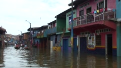People paddling canoe between the colorful  houses in the floating village Stock Footage