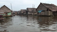 People paddling canoe between the houses in the floating village in Amazon Stock Footage