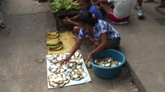 Woman selling fish sitting on ground on market Stock Footage