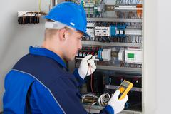 Male Technician Examining Fusebox With Digital Insulation Resistance Tester Stock Photos