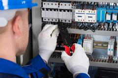 Close-up Photo Of Male Electrician Repairing Fusebox Stock Photos