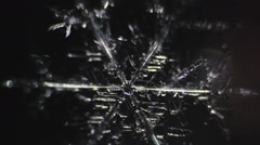 Beautiful transparent shiny snowflake on a dark background Stock Footage