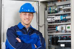 Portrait Of A Happy Young Male Electrician Standing In Front Of Fusebox Stock Photos