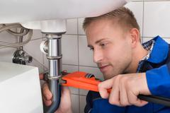 Young Male Plumber Fixing Sink In Kitchen Stock Photos