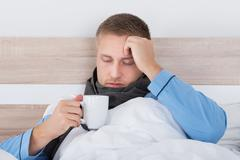 Young Man In Bed With Blanket And A Cup Of Hot Beverage - stock photo
