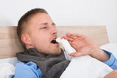 Stock Photo of Close-up Of Young Man Using Asthma Inhaler On His Bed