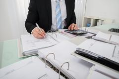 Photo Of Young Businessman Calculating Bill In Office - stock photo