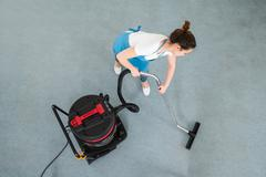 Young Female Janitor Cleaning Floor With Vacuum Cleaner - stock photo