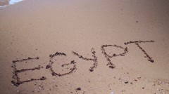 Word egypt on sand with wave Stock Footage