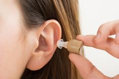 Close-up Of A Woman Hands Putting Hearing Aid In Ear - stock photo
