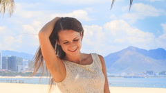 Slim girl in white frock smiles smoothes hair on beach Stock Footage