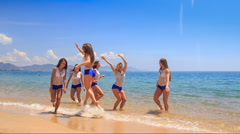Cheerleaders in white blue jump run along shallow water Stock Footage