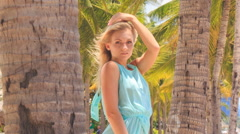 blonde girl in azure lowers hands along body among palms - stock footage