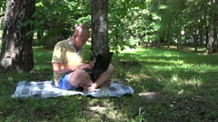 Successful freelancer worker man working with notebook in park. 4K Stock Footage