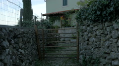 View of a wooden fence and stonewalls in front of a house, Krk Island Stock Footage