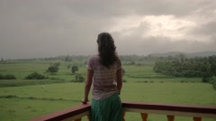 Long haired girl looking at landscape from balcony - stock footage