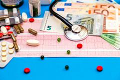 Stethoscope on cardiogram sheet with Euro bills and pills. - stock photo
