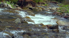 Mountain river with waterfalls and rapids flowing between rocky river banks - stock footage