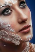 Woman looking up with bridal extravagant make up - stock photo