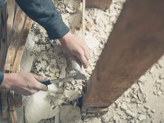 Person using hammer in rubble - stock photo