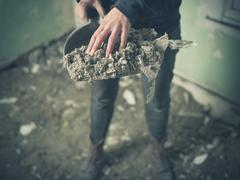 Hand with dustpan full of rubble Stock Photos