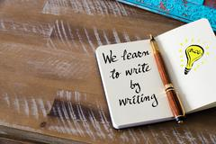 Handwritten text WE LEARN TO WRITE BY WRITING - stock photo