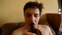 A Drunk young man drink a beer at home Stock Footage