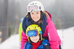 Sweet young boy and his mother, learning to ski on a mild ski slope in Austri Stock Photos