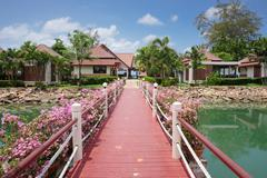 Bridge with flowers across the bay in a tropical garden - stock photo