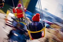 Kids, having fun on a swing chain carousel ride Stock Photos