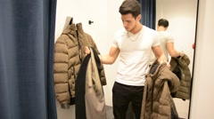 Young Man Trying on Clothes in Clothing Store Stock Footage